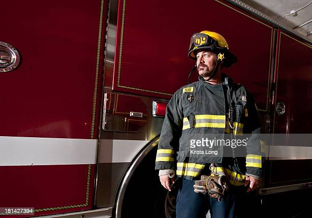 a firefighter standing in front of a fire truck - firefighter stock pictures, royalty-free photos & images