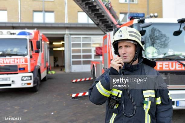 firefighter standing on yard at fire engine using walkie talkie - fire station - fotografias e filmes do acervo