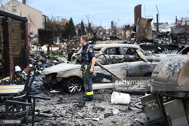 Firefighter stands among the remains of homes burned down in the Rockaway neighborhood during Hurricane Sandy on October 31, 2012 in the Queens...