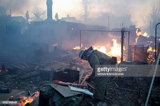 A firefighter stands amongst rubbles and flames after shelling destroyed several houses in the district of Kuibishevskiy near the airport in the...