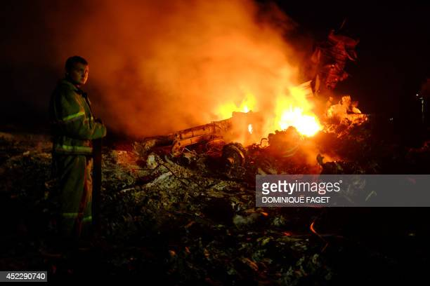 A firefighter stands as flames burst amongst the wreckages of the malaysian airliner carrying 298 people from Amsterdam to Kuala Lumpur after it...