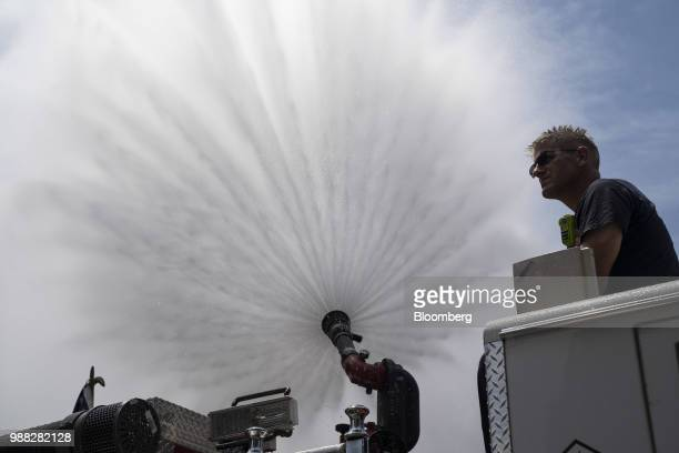 A firefighter stands as water is sprayed from a hose during a protest against the Trump administration's policy on separating immigrant families at...