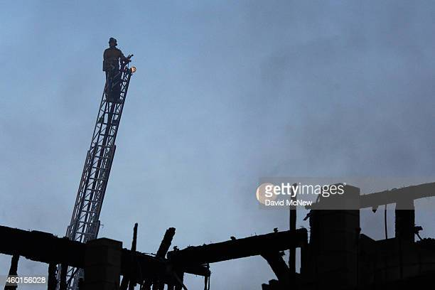 A firefighter stands atop a ladder truck with the moon in the background during a fire that destroyed a sevenstory apartment building under...