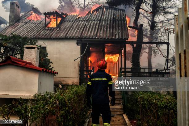 A firefighter stands in front of a burning house during a wildfire in Kineta near Athens on July 23 2018 More than 300 firefighters five aircraft and...