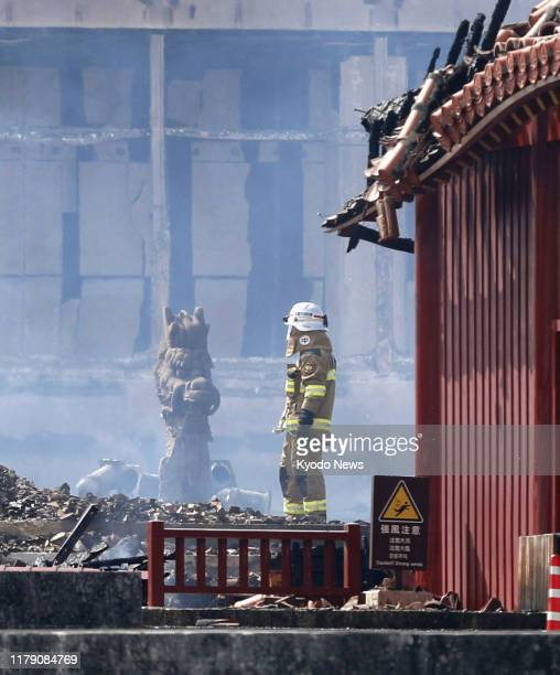 A firefighter stands in front of the Seiden main hall of Shuri Castle in Naha Okinawa Prefecture southern Japan on Oct 31 after it was razed by a...