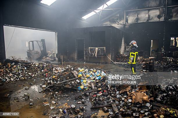 A firefighter stands inside an entirely burnt warehouse belonging to French charity 'Restos du Coeur' on December 2 2014 in VendinleVieil AFP PHOTO...