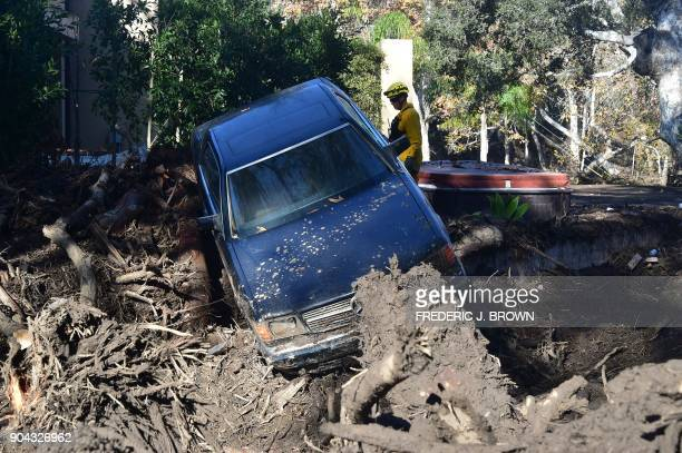 A firefighter stands near a car caught up in a mud slide in Montecito California January 12 2018 Heavy rains on January 9 sent rivers of waisthigh...