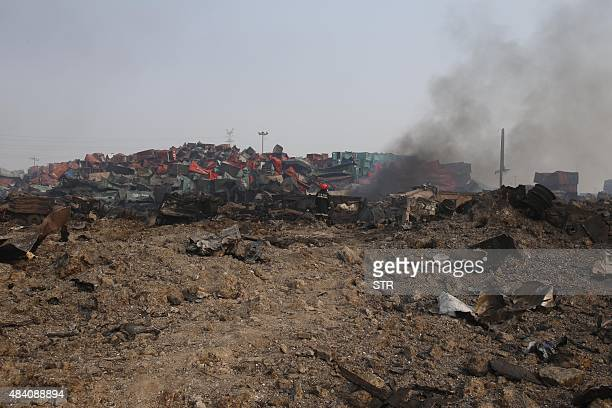 A firefighter stands next to a wreckage at the site of the explosions in Tianjin on August 15 2015 Residents near the site of two giant explosions in...