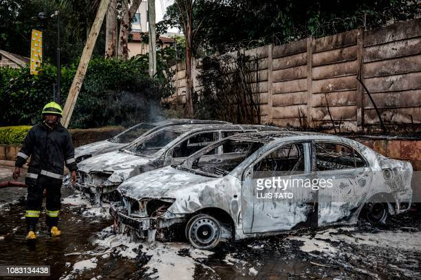 A firefighter stands next to the wreckage of cars following an explosion at a hotel complex in Nairobi's Westlands suburb on January 15 in Kenya The...