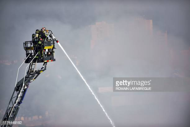 Firefighter stands on a ladder spraying liquid from a hose as he joins colleagues attempting to control a factory fire in Villeurbanne,...