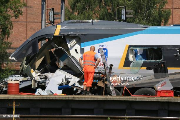 A firefighter stands on a truck by a damaged train after a train collided with a truck at a level crossing on July 22 2015 in Studenka Czech Republic...