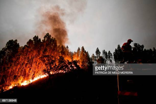 A firefighter stands on top of a fire combat truck during a wildfire at Penela Coimbra central Portugal on June 18 2017 A wildfire in central...
