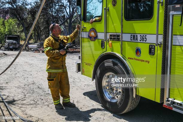 A firefighter stands outside his truck while working on the power lines that were destroyed in the Clayton Fire in Lower Lake California August 16...