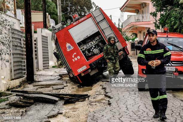 A firefighter stands outside his vehicle that fell into a hall of a damaged road after a havy rainfall causing floods near Corinth on September 30...