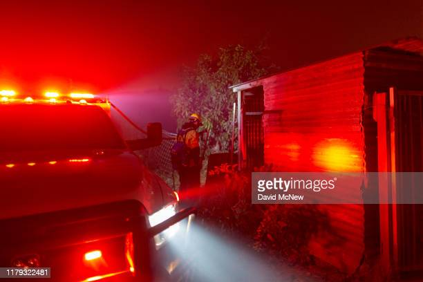 A firefighter stands watch at an avocado farm as the Maria Fire explodes to 8000 acres on its first night on November 1 2019 near Somis California...