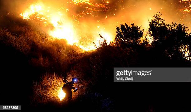 A firefighter starts a back fire along San Gabriel Canyon Road in Azusa as the Colby fire burns through brush Thursday