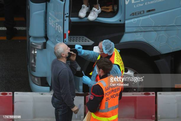 Firefighter swabs a lorry driver to test for Covid-19 on December 24, 2020 in Dover, United Kingdom. Travel from the UK to France is gradually...