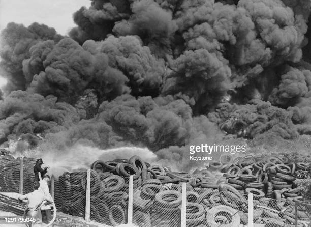 Firefighter tackles a blaze as clouds of black smoke billow from a burning rubber tyre dump on St John's Road in New Malden, London, England, 22nd...