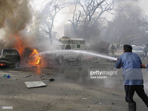 A firefighter tackles blazing cars after a powerful car bomb exploded outside a Christian school on January 15 2004 in Karachi Pakistan The blast...