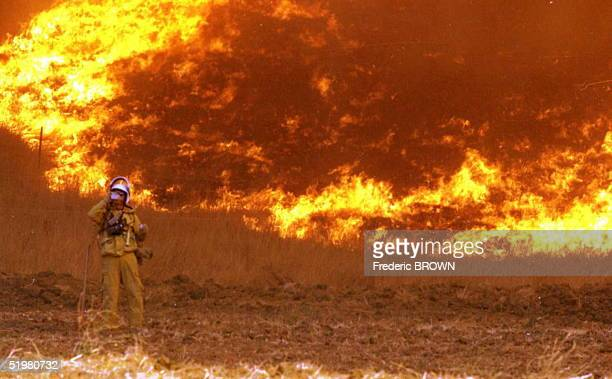 A firefighter takes a break to drink some water against a wall of fire burning near Calabasas near Malibu Cayon California 21 October Gusty winds...