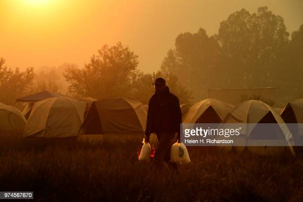 A firefighter takes ice to his crew as he makes his way through fire camp before heading back out on the fire line of the 416 Fire on June 14 2018 in...