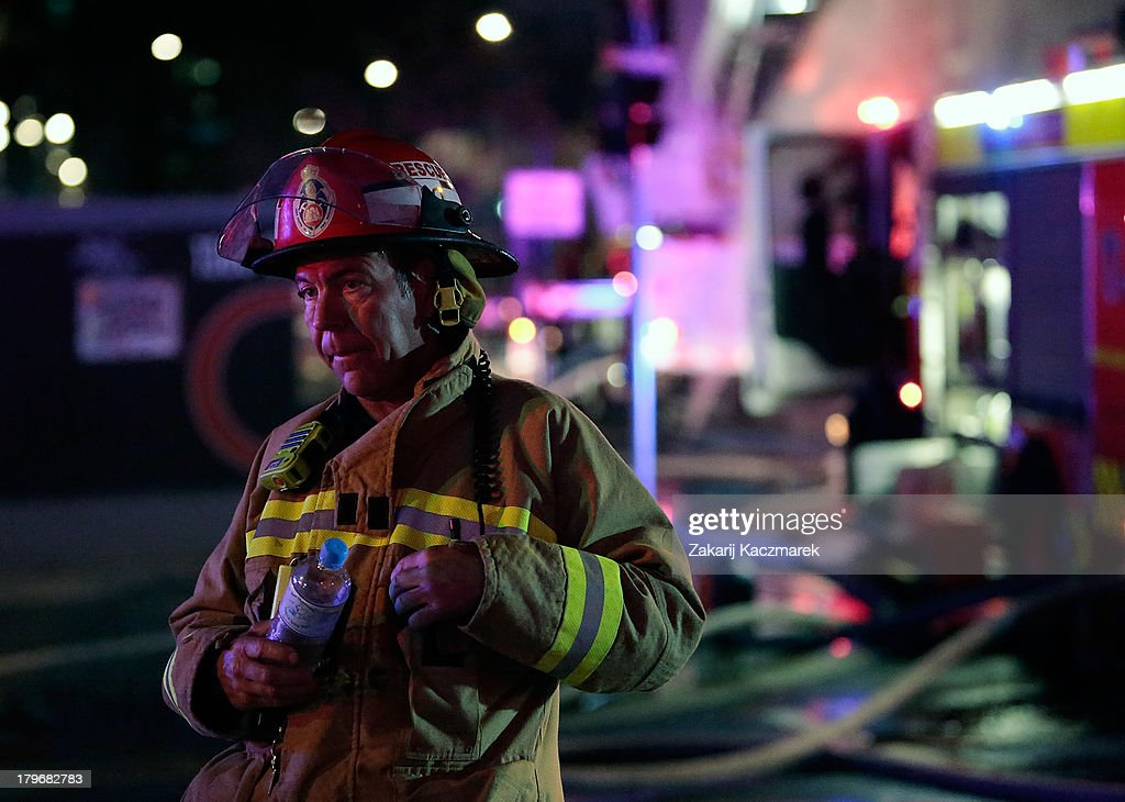 A firefighter takes respite during efforts to bring a fire under control in O'Connor Street, Chippendale, a mixed residential and commercial area, on September 6, 2013 in Sydney, Australia.