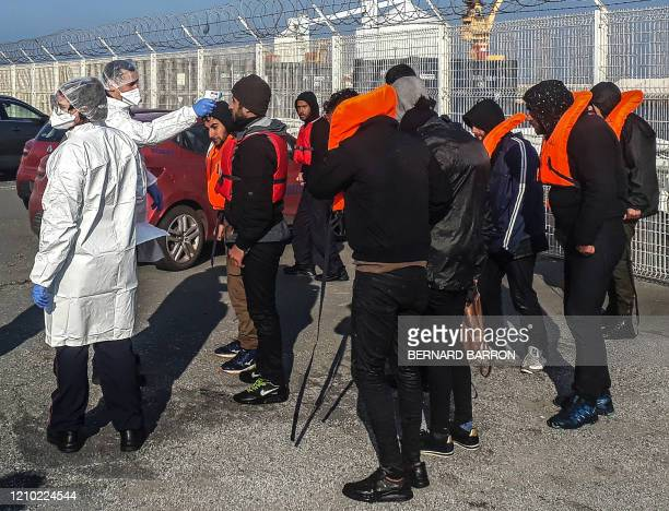 Firefighter takes the temperature to migrants who were recsued off the coast of Calais while trying to cross to Great Britain on April 17 during the...