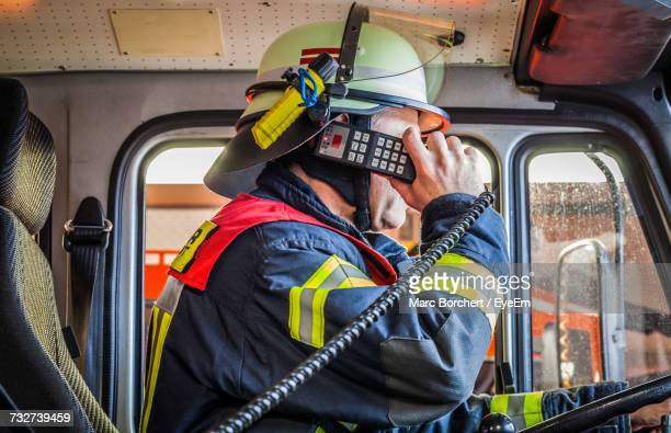 Firefighter Talking On Walkie-Talkie While Sitting Fire Engine