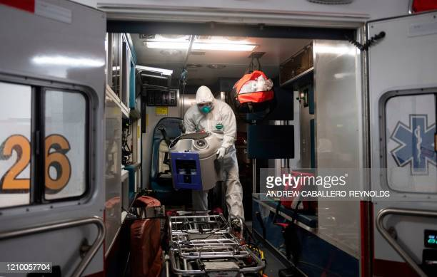 TOPSHOT Firefighter technician Jimmy McDuffie sets up a decontamination system inside an ambulance after it was exposed to a suspected COVID19 case...
