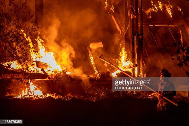 A firefighter tends to a structure lost during the Kincade fire off Highway 128 east of Healdsburg California on October 29 2019 California braced on...