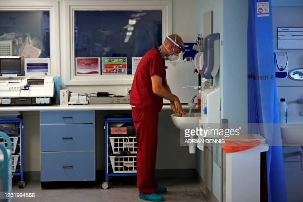 Firefighter Tom Ventress washes his hands after tending to a Covid-19 patient alongside critical care nurses in the Intensive Care Unit at Queen...