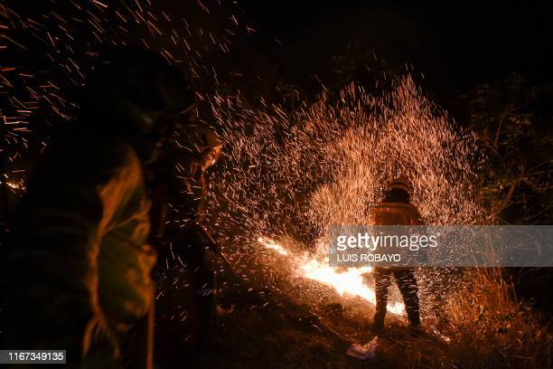 TOPSHOT A firefighter tries to extinguish a wildfire in rural area of Cali Colombia on September 10 2019 During this year there have been about 526...