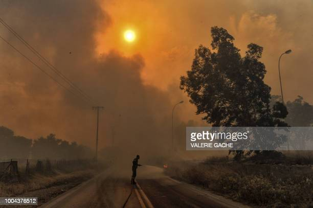 TOPSHOT A firefighter tries to extinguish hotspots during a wildfire in Kineta near Athens on July 23 2018 More than 300 firefighters five aircraft...