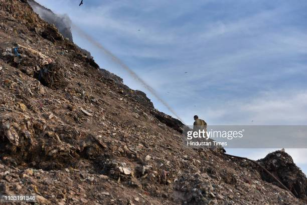A firefighter tries to extinguish the fire at Bhalswa Landfill site on March 27 2019 in New Delhi India