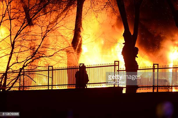 A firefighter tries to put out a fire as Turkish army busses burn after an explosion on February 17 2016 in Ankara Turkey At least five people have...