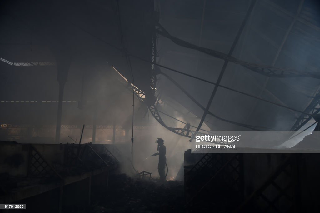 TOPSHOT - A firefighter tries to put out the blaze which destroyed the Iron Market in Port-au-Prince on February 13, 2018. Fire ravaged a historic market leaving burned-out merchants fearing for their livelihoods in the impoverished nation.The Iron Market was rebuilt in 2011 after the 2010 Haiti eartquake. There were no immediate reports of casualties nor the cause of the fire. /