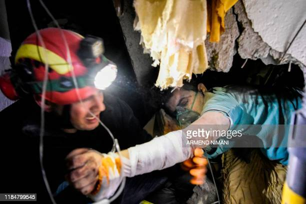 Firefighter tries to rescue a man stucked in the ruins of a collapsed building in Thumane, northwest of capital Tirana, after an earthquake hit...