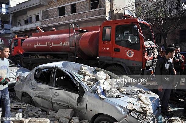A firefighter truck is seen next to a destroyed car at the site of a car bomb explosion in alZahra neighborhood in Homs on December 12 2015 Fifteen...