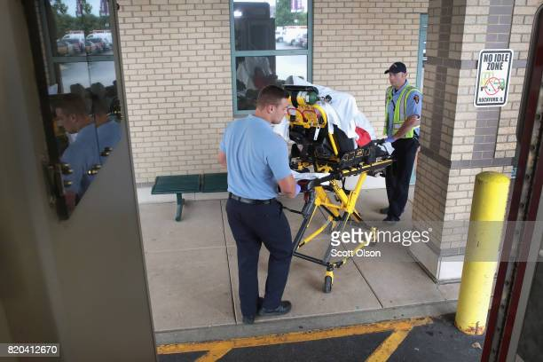 Firefighter Tyler Behrends and Brian Maschke bring an overdose victim into a hospital on July 14 2017 in Rockford Illinois The woman was found on the...