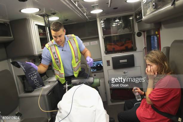 Firefighter Tyler Behrends treats a women suspected of overdosing on heroin on July 14 2017 in Rockford Illinois Residents called for an ambulance...