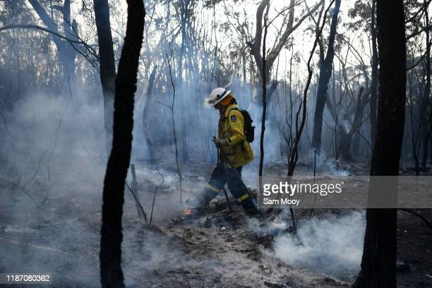 RFS firefighter undertakes mopping up at South Turramurra on November 12 2019 in Sydney Australia More than 60 fires are burning across NSW with 200...