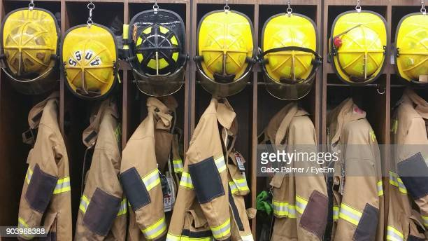 firefighter uniforms with helmet hanging in rack - firefighter stock pictures, royalty-free photos & images
