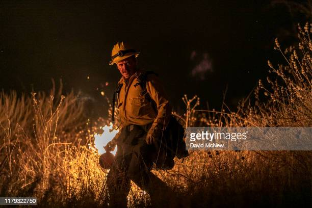 A firefighter uses a drip torch to start a backfire as the Maria Fire explodes to 8000 acres on its first night on November 1 2019 near Somis...