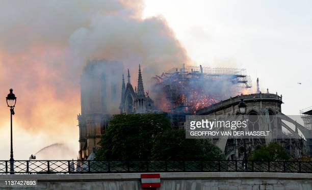 A firefighter uses a hose to douse flames and smoke billowing from the roof at NotreDame Cathedral in Paris on April 15 2019 A fire broke out at the...