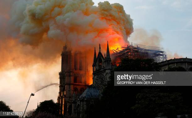 TOPSHOT A firefighter uses a hose to douse flames and smoke billowing from the roof at NotreDame Cathedral in Paris on April 15 2019 A fire broke out...