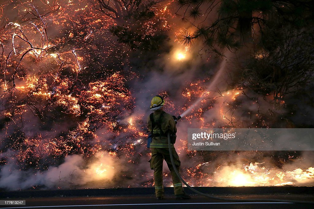 A firefighter uses a hose to douse the flames of the Rim Fire on August 24, 2013 near Groveland, California. The Rim Fire continues to burn out of control and threatens 4,500 homes outside of Yosemite National Park. Over 2,000 firefighters are battling the blaze that has entered a section of Yosemite National Park and is currently 5 percent contained.