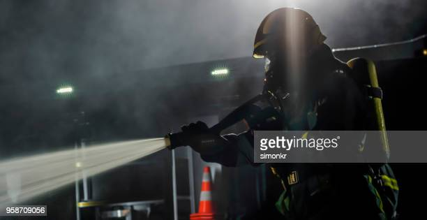 firefighter using extinguisher - fire protection suit stock pictures, royalty-free photos & images