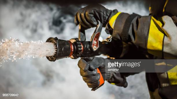 firefighter using extinguisher - firefighter stock pictures, royalty-free photos & images