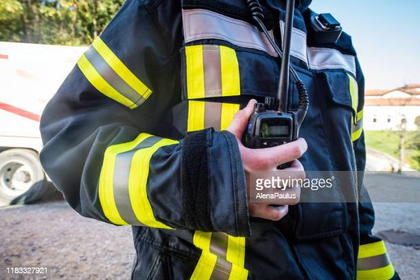 firefighter using walkie talkie, rescue operation close up - radio stock pictures, royalty-free photos & images