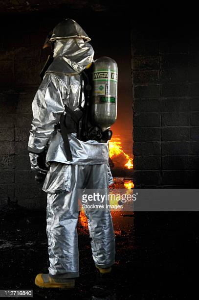 a firefighter waits for a fire to get bigger before attempting to extinguish the flames. - fire protection suit - fotografias e filmes do acervo